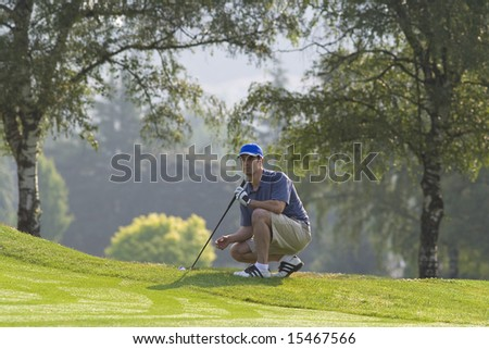 Man squatting off green lining up golf shot - Horizontally framed photo