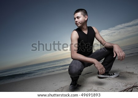 Man squatting on the beach during dawn