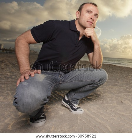stock-photo-man-squatting-on-the-sand-30958921.jpg