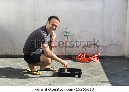 Man squatting over paint tray with hose in background. Man wearing shorts and sandals. Horizontally framed photo.