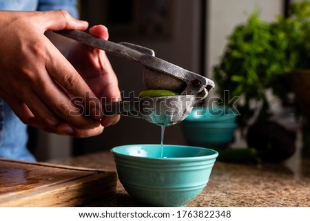 Man squeezing lime with a metal squeezer into a bowl. Foto d'archivio ©