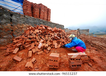 Man stack up bricks at construction site during winter cold weather