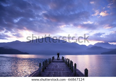 Man stand on a pier and watching the mountains and lake - stock photo