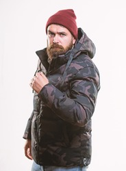 Man stand warm camouflage pattern jacket parka with hood isolated on white background. Hipster winter fashion. Winter stylish menswear. Comfortable winter outfit. Guy wear hat and black winter jacket.