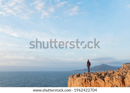 Man standing against the sea on a high cliff looking at the panorama. Sunset view on the water. ストックフォト ©