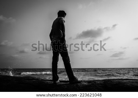 Man standing alone on a rock at the beach,Black and white