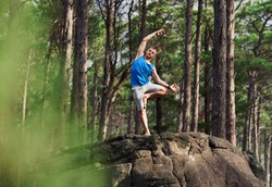 Man standing alone on a rocky outcrop in a pine forest doing the bending tree pose while practicing yoga