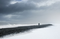 Man standing alone on the dark and snow beach under cloudy sky and wild sea