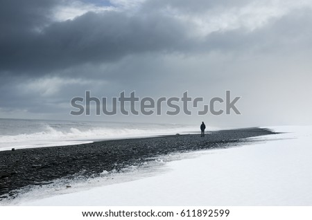 Man standing alone on the dark and snow beach under cloudy sky and wild sea #611892599