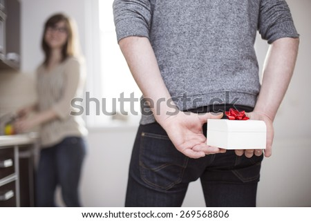 Man standing and holding white gift box behind his back #269568806