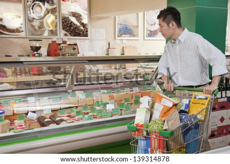 Man standing and looking at the Deli counter, Beijing