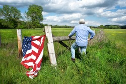 man standing at barbwire fence in grassy field with American flag, farmer, patriotic, democracy, America, conservative, freedom, business, Memorial Day, Veterans Day