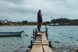 man standing at edge of the small fishing pier looking at stormy sea. overcast weather. sadness