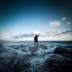 Man standing at sea shore facing incoming storm and waves