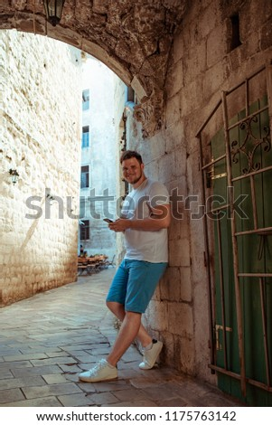 man standing at street in kotor town with mobile phone, montenegro
