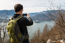 Man standing back view. Young man taking a photo by phone. View from the hill to Lake Bled, the island of Bled and the church. Slovenian lake surrounded by mountains, the Alps and forest. Slovenia