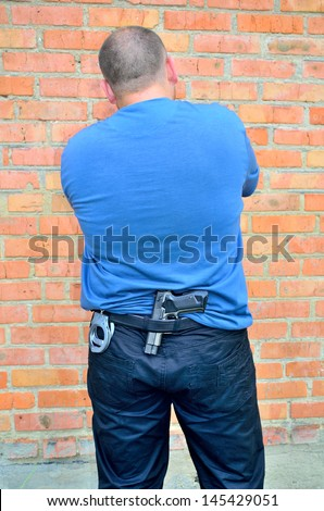 man standing back with a pistol and handcuffs in his belt on a brick wall