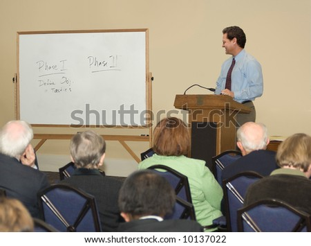 Man standing behind a podium, looking at a whiteboard before a group of adults