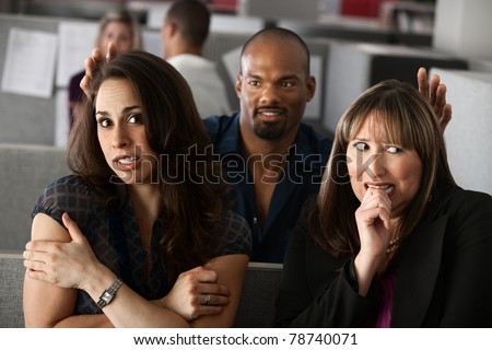 Man standing behind two scared women in office cubicle