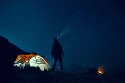 Man standing beside camping tent wearing headlamp during nighttime.