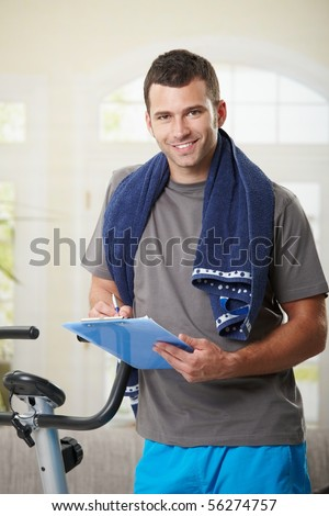 Man standing beside stationary bike after finishing exercise, making notes in training plan.