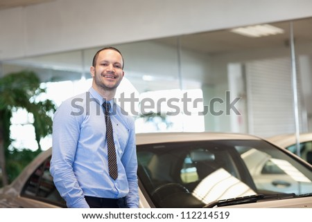 Man standing between cars in a dealership