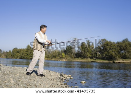 Man Standing By A River With A Fishing Pole