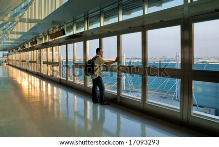 Man standing by a window and waiting his flight, Pearson International Airport, Toronto, Canada.