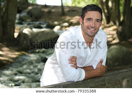Man standing by a woodland stream