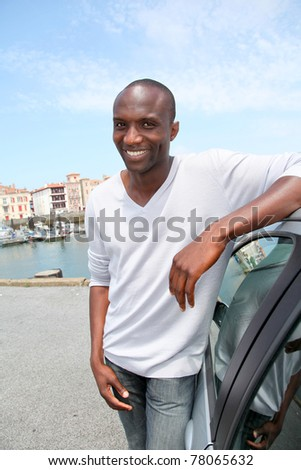 Man standing by car in tourist town