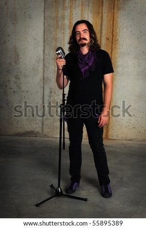 Man standing by vintage microphone in industrial grunge background