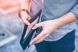 Man standing holding black wallet full of money