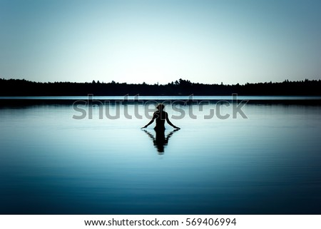 Man standing in a pond contemplating about life.