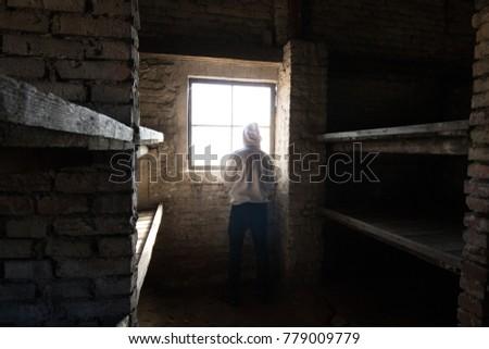 Man standing in front of a window in Auschwitz Birkenau cabin