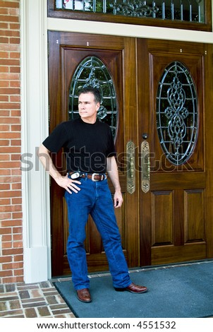 Man standing in front of beautiful wooden double doors with ornate glass work.