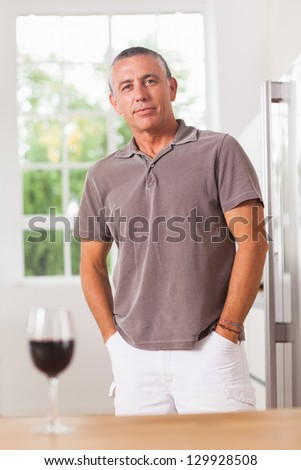 Man standing in kitchen behind table and glass of red wine - stock photo