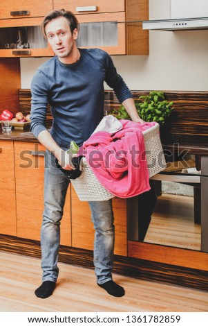 Man standing in kitchen with laundry basket in hands. Housework concept. #1361782859