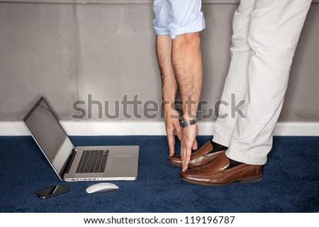Man standing in office doing exercises with laptop - landscape interior.