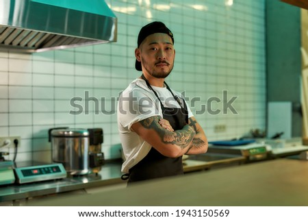 Man standing in the kitchen and looking at the camera. Young asian chef ready to cooking delicious food. Cook with folded hands posing in the cuisine. Restaurant work concept