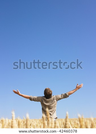 Man standing in wheat field with arms outstretched. Vertically framed shot.