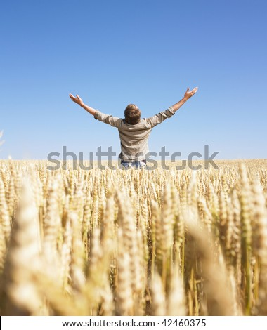 Man standing in wheat field with arms raised. Vertically framed shot.