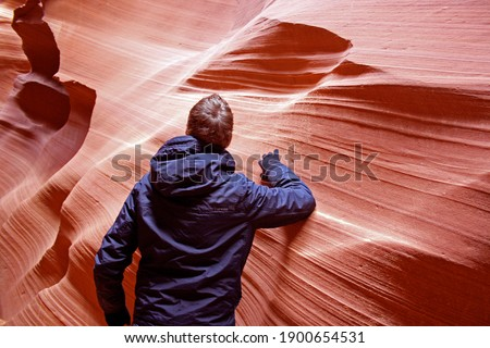 Man standing inside beautiful Antelope slot canyon, Page, Arizona. Guy with gloves and winter jacket hiking through narrow pathways in between smooth sand stone formations. Stock photo ©