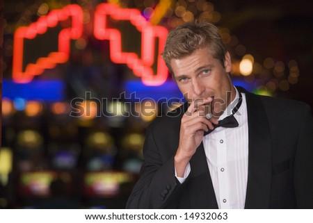 Man standing inside casino smoking cigar