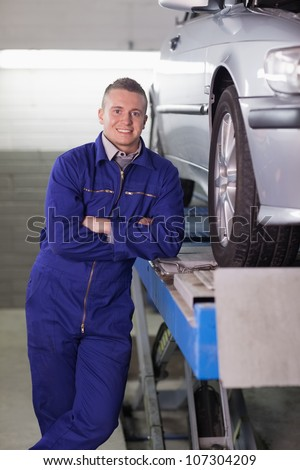 Man standing next to a car in a garage stock photo 107304209