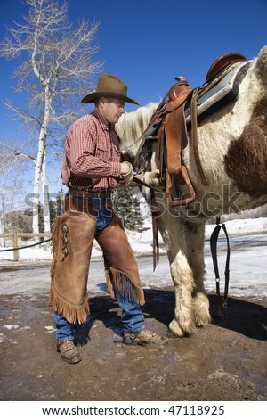 Man standing next to a horse while cinching up a saddle. Vertical shot.