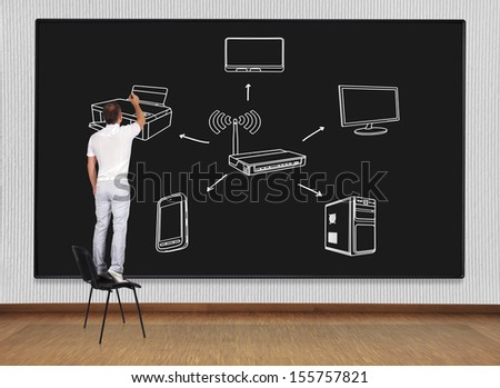man standing on a chair and drawing computer network