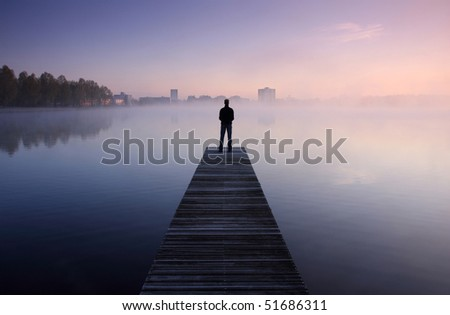 Man standing on a jetty looking at a city over foggy water at dawn.