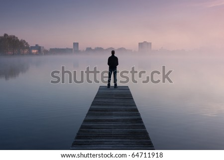 Man standing on a jetty on an early autumn morning
