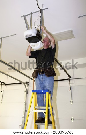 Man standing on a ladder fixing a mechanical garage door opener