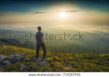 Man standing on a mountain hill and contemplate the sunset above Crimea mountains.